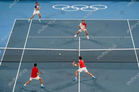 Nikola Mektic, bottom right, and Mate Pavic, of Croatia, return to Marin Cilic, top left, and Ivan Dodig, of Croatia, during the final round of the men's doubles tennis competition at the 2020 Summer Olympics, in Tokyo, Japan