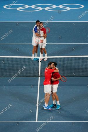 Nikola Mektic, bottom left, and Mate Pavic, of Croatia, react after defeating Marin Cilic, top left, and Ivan Dodig, of Croatia, during the final round of the men's doubles tennis competition at the 2020 Summer Olympics, in Tokyo, Japan