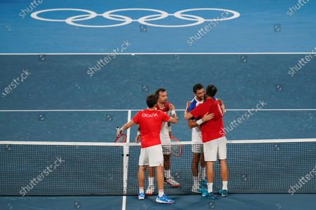Nikola Mektic, left, and Mate Pavic, right, of Croatia, embrace Ivan Dodig, second from left, and Marin Cilic, of Croatia, after defeating them in the final round of the men's doubles tennis competition at the 2020 Summer Olympics, in Tokyo, Japan
