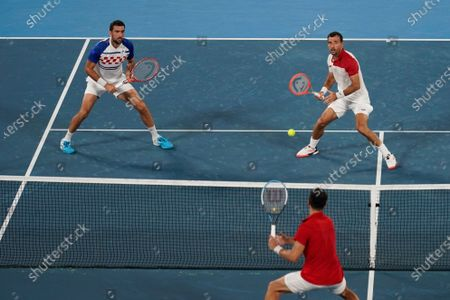 Stock Image of Marin Cilic, top left, and Ivan Dodig, of Croatia, prepare to return to Nikola Mektic and Mate Pavic, of Croatia, during the final round of the men's doubles tennis competition at the 2020 Summer Olympics, in Tokyo, Japan