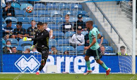 QPR Goalkeeper Seny Dieng clears ahead of Jamie Vardy of Leicester City