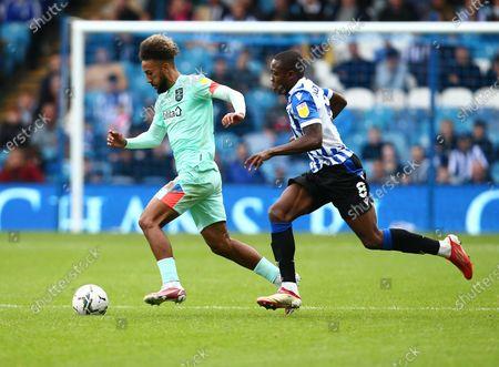 Sorba Thomas of Huddersfield Town and Dennis Adeniran of Sheffield Wednesday