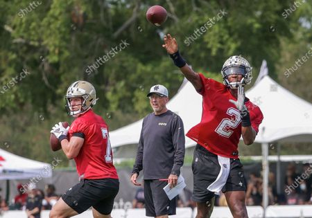New Orleans Saints quarterback Jameis Winston (2) and quarterback Taysom Hill (7) throw as offensive coordinator Pete Carmichael watches during NFL football training camp in Metairie
