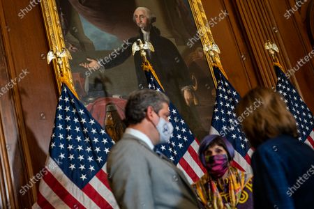 A painting of President George Washington hangs overhead as Speaker of the House Nancy Pelosi (D-CA) speaks with other lawmakers after a bill enrollment ceremony for Security Supplemental to the January 6th Appropriation Act in the Rayburn Room of the U.S. Capitol Building on Friday, July 30, 2021 in Washington, DC. (Kent Nishimura / Los Angeles Times)