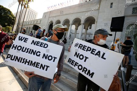 """Chris Venn, left, and Michal Lindley, right, join people gather for The Right to REST without ARREST Rally and Press Conference on the steps of Los Angeles City Hall Wednesday organized by homeless advocates across LA including UTACH, LACAN, LATU, Ground Game LA, Street Watch LA, Union de Vecinos, Reclaiming our Homes, and members of the SNS coalition. The groups are protesting LA City Council's second hearing of Mark Ridley Thomas' 41.18 alternate motion which will give council the authority to ban sitting, lying down, and sleeping on large swaths of LA sidewalks - leaving the unhoused asking the question, """"Where will we go?"""" City Hall on Wednesday, July 28, 2021 in Los Angeles, CA. (Al Seib / Los Angeles Times)."""