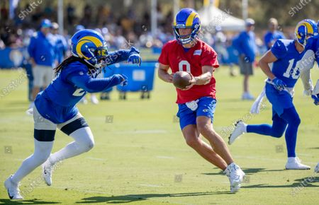 Rams starting quarterback Matthew Stafford looks to hand-off to running back Darrell Henderson Jr. (27) on the first day of training camp at UC Irvine on July 28, 2021 in Irvine, California.(Gina Ferazzi / Los Angeles Times)