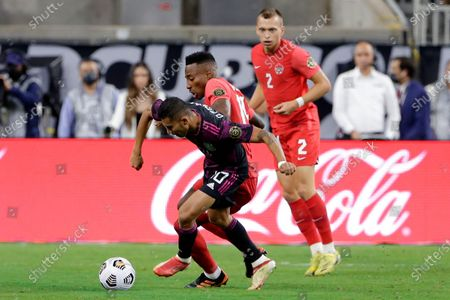 Mexico midfielder Orbelin Pineda (10) and Canada defender Mark-anthony Kaye, middle, battle for the ball as defender Alistair Johnston (2) looks on during the first half of a CONCACAF Gold Cup soccer semifinal, in Houston