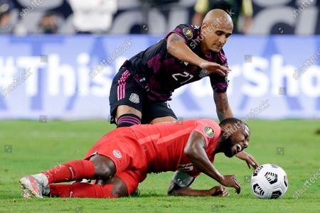 Canada forward Junior Hoilett, bottom, reacts after being pulled down by Mexico defender Luis Rodriguez (21) during the second half of a CONCACAF Gold Cup soccer semifinal, in Houston