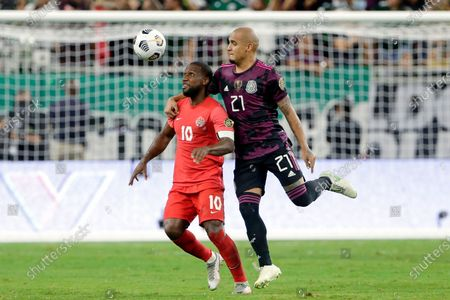 Canada forward Junior Hoilett (10) is pulled back by Mexico defender Luis Rodriguez (21) as they chase the ball during the second half of a CONCACAF Gold Cup soccer semifinal, in Houston