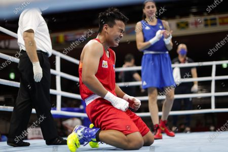 Philippines' Nesthy Petecio, center, reacts after winning a women's featherweight 57-kg boxing semifinal match against Italy's Irma Testa, right, at the 2020 Summer Olympics, in Tokyo, Japan