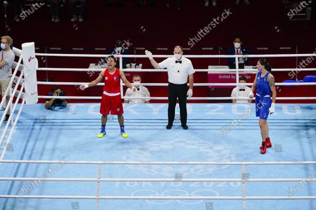 Philippines' Nesthy Petecio celebrates after winning her women's featherweight 57-kg semifinal boxing match against Italy's Irma Testa, right, at the 2020 Summer Olympics, in Tokyo, Japan