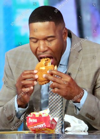 Stock Image of Michael Strahan on Good Morning America seen having a Bojangles chicken sandwich