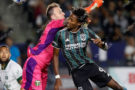 Galaxy forward Kevin Cabral, right, is fouled by Portland Timbers goalkeeper Steve Clark on a header, resulting in a penalty kick during the second half of an MLS soccer match in Carson, Calif