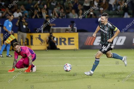 Galaxy midfielder Sacha Kljestan, right, runs past Portland Timbers goalkeeper Steve Clark after scoring on a penalty kick during the second half of an MLS soccer match in Carson, Calif