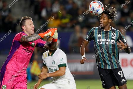 Galaxy forward Kevin Cabral (9) heads the ball against Portland Timbers goalkeeper Steve Clark, left, during the second half of an MLS soccer match in Carson, Calif