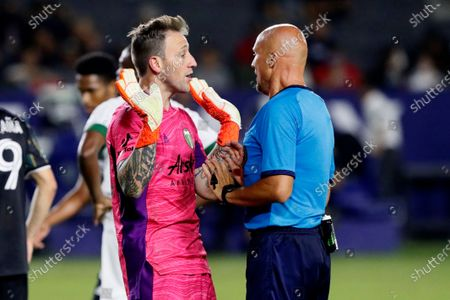 Portland Timbers goalkeeper Steve Clark, left, talks with referee Robert Sibiga during the second half of an MLS soccer match against the LA Galaxy in Carson, Calif