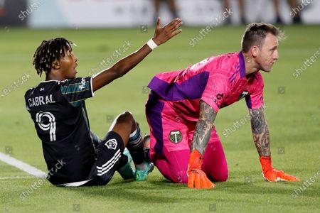 Galaxy forward Kevin Cabral (9) pleads for a foul call by the referee against Portland Timbers goalkeeper Steve Clark, right, during the second half of an MLS soccer match in Carson, Calif
