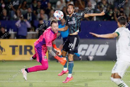 Galaxy forward Ethan Zubak (29) centers a head ball past Portland Timbers goalkeeper Steve Clark, left, during the second half of an MLS soccer match in Carson, Calif