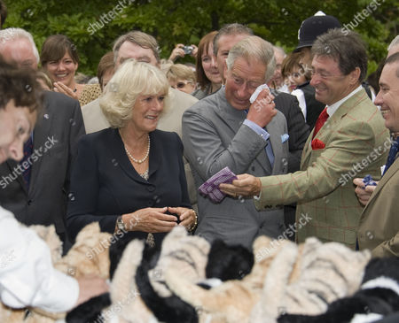 Camilla Duchess of Cornwall and Prince Charles are handed a handkerchief by Alan Titchmarsh