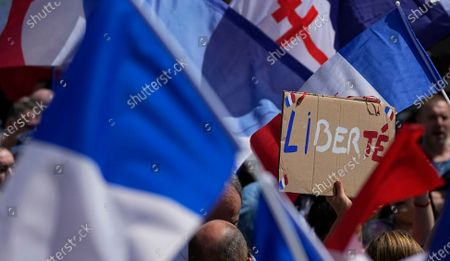 Protestor waves a sign which reads 'freedom' in the middle of French flags during a demonstration in Paris, France, . Demonstrators gathered in several cities in France on Saturday to protest against the COVID-19 pass, which grants vaccinated individuals greater ease of access to venues