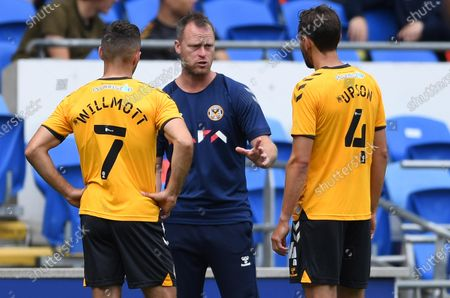 Newport County manager Michael Flynn talks to Robbie Willmott and Ed Upson of Newport County.