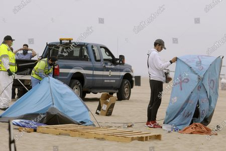 """Stock Picture of VENICE, CA - JULY 30, 2021 - - Michael Freeman, 19, packs up his tent as sanitation crews prepare to clear debris and encampments in Venice on July 30, 2021. Freeman, originally from New Orleans, has been living homeless in California for 6 years and for the past few months in Venice. """"Hope to get a job. Have a family. Make a living,"""" is what he hopes for. St. Joseph's Center found him a room to stay in as part of Project Roomkey. """"Venice Beach had been one of the craziest times I've lived,"""" he said as he left the beach, with a skateboard over his shoulder. Over a dozen sanitation workers with the City of Los Angeles and contract workers with Beaches and Harbors clear homeless encampments and debris a few yards at a time on the beach near Thornton Avenue and Ocean Front Walk. The sweep began around 8 a.m. as members of St. Joseph Center and LAHSA tried to arrange housing for homeless who have been living on the beach. (Genaro Molina / Los Angeles Times)"""