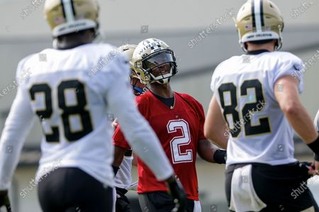 New Orleans Saints quarterback Jameis Winston (2) talks with tight end Adam Trautman (82) and running back Latavius Murray (28) during NFL football training camp in Metairie