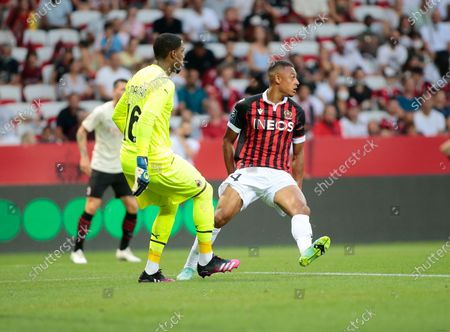 Mike Maignan of AC Milan and Dan Ndoye of OGC Nice during the friendly match between OGC Nice and AC Milan at Alliance Riviera.