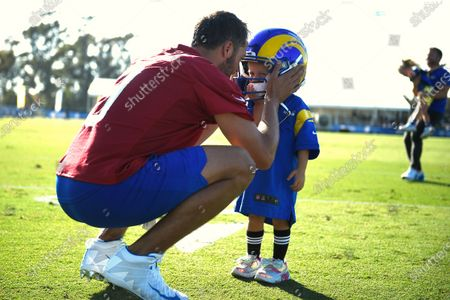 Los Angeles Rams quarterback Matthew Stafford speaks with his daughter as she wears his helmet after NFL football training camp practice in Irvine, Calif