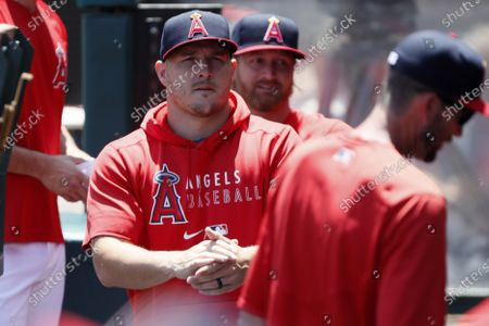 Los Angeles Angels' Mike Trout looks over from the dugout before a baseball game against the Oakland Athletics in Anaheim, Calif