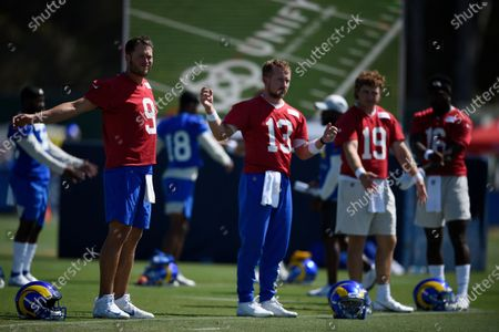 Los Angeles Rams quarterbacks Matthew Stafford, left to right, stretches with John Wolford, Devlin Hodges and Bryce Perkins during an NFL football training camp practice in Irvine, Calif