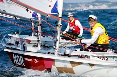 Winner Anne-Marie Rindom of Denmark and second placed Josefin Olsson (rear) of Sweden after the medal race in the Women's One Person Dinghy Laser during the Sailing events of the Tokyo 2020 Olympic Games in Enoshima, Japan, 01 August 2021.