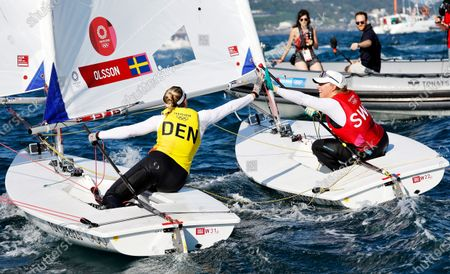 Winner Anne-Marie Rindom (L) of Denmark celebrates with second placed Josefin Olsson of Sweden after the medal race in the Women's One Person Dinghy Laser during the Sailing events of the Tokyo 2020 Olympic Games in Enoshima, Japan, 01 August 2021.