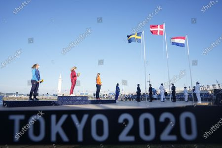 Stock Photo of From left, second placed Sweden's Josefin Olsson, first placed Denmark's Anne-Marie Rindom and third placed Netherlands'Marit Bouwmeester celebrate at the end of the women's laser medal race at the 2020 Summer Olympics, in Fujisawa, Japan