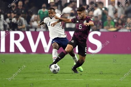 United States midfielder Kellyn Acosta (23) battles for the ball with Mexico midfielder Jonathan Dos Santos (6) during the first half of the CONCACAF Gold Cup final soccer match, in Las Vegas