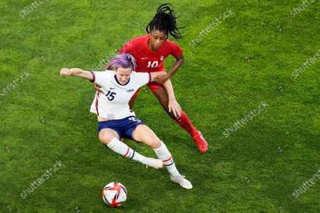 United States' Megan Rapinoe, left, and Canada's Ashley Lawrence battle for the ball during a women's semifinal soccer match at the 2020 Summer Olympics, in Kashima, Japan