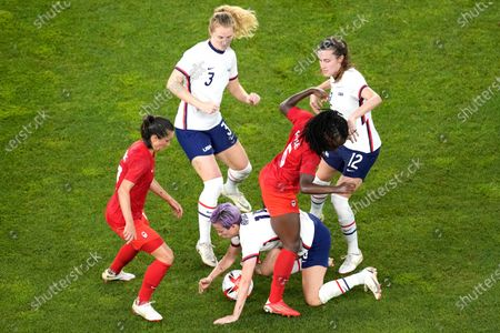 United States' Megan Rapinoe, below, and Canada's Deanne Rose battle for the ball during a women's semifinal soccer match at the 2020 Summer Olympics, in Kashima, Japan