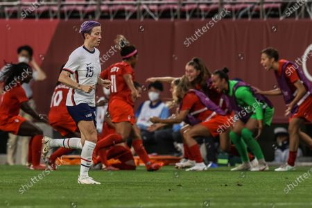 Tokyo, Japan, Monday, August 2, 2021 - Team United States forward Megan Rapinoe (15) jogs past the celebration as Canada players swarm midfielder Jessie Fleming (17) after she scored on a penalty kick for a 1-0 lead over USA at Ibaraki Kashima Stadium. (Robert Gauthier/Los Angeles Times)
