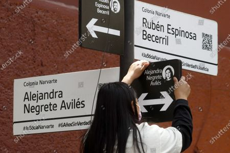 Gabriela Mejia daughter of a the victim Alejandra Negrete post a sticker with the name of her mother in honor  of murdered  victims, activist Nadia Vera, domestic worker Alejandra Negrete, beauty student Yesenia Quiroz, model Mile Martin and photojournalist Ruben Espinosa, that they were killed with firearm shots,  inside of  department of the 1909 building, on Luz Savinon street in  Narvarte neighborhood 6 years ago. Relatives take part during a protest to demand Justice for the  multihomicide. On July 31, 2021 in Mexico City, Mexico.