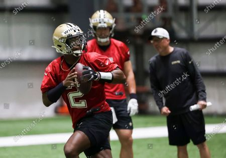 Stock Photo of New Orleans Saints quarterback Jameis Winston (2) throws as quarterback Taysom Hill (7) watches during NFL football training camp in Metairie