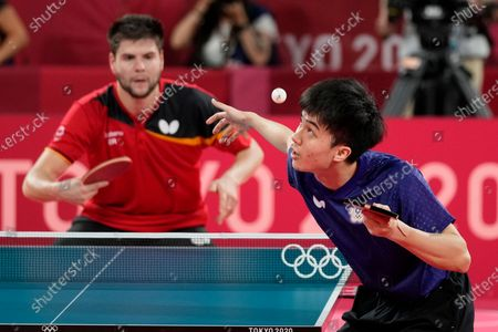 Taiwan Lin Yun-ju, right, compete during the table tennis men's team quarterfinal against Germany's Dimitrij Ovtcharov at the 2020 Summer Olympics, in Tokyo, Japan