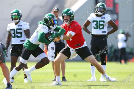 Stock Photo of New York Jets quarterback James Morgan (4) hands the ball to running back Tevin Coleman (23) during practice at the team's NFL football training facility, in Florham Park, N.J