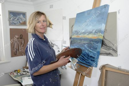 Suzanne Lloyd with some of the paintings she is trying to sell to raise money for treatment