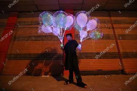 A boy sells balloons in front of a closed market as the government reduces market business hours after new cases of COVID-19 were reported across the country in Peshawar, Pakistan, 03 August 2021. Countries around the world are taking increased measures to stem the widespread of the COVID-19 disease.