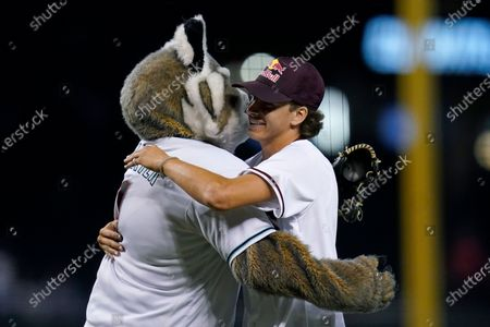"""Jagger Eaton, right, the Olympic bronze medalist the the United State for men's street competition in skateboarding in the 2021 Tokyo Olympics, of Mesa, Ariz., gets a hug from Arizona Diamondbacks mascot """"Baxter"""" after Eaton threw out the first pitch prior to a baseball game between Diamondbacks and the San Francisco Giants, in Phoenix"""