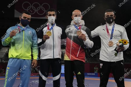 From left, silver medalist, Ukraine's Parviz Nasibov, gold medalist, Iran's Mohammedreza Geraei, bronze medalist, Germany's Frank Staebler and bronze medalist, Mohamed Ibrahim Elsayed of Egypt celebrate on the podium during the medal ceremony for the men's 67kg Greco-Roman wrestling at the 2020 Summer Olympics, in Chiba, Japan