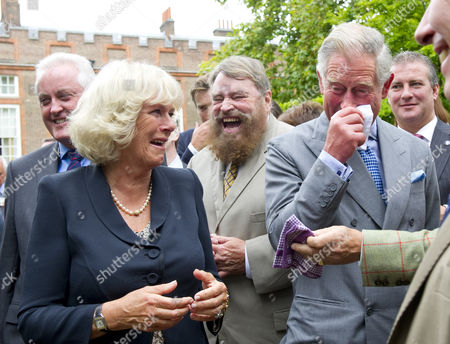 Prince Charles, Camilla Duchess of Cornwall and Brian Blessed are caught in a fit of giggles as they watch a cat organ