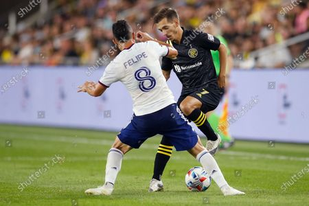 Stock Image of Columbus Crew's Pedro Santos, right, controls the ball in front of D.C. United's Felipe Martins during the second half of an MLS soccer match, in Columbus, Ohio