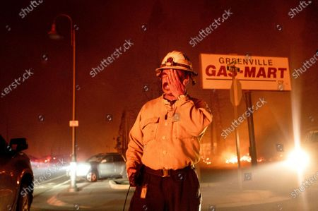 Stock Photo of Battalion Chief Sergio Mora rubs his face as the Dixie Fire tears through the Greenville community of Plumas County, Calif., on . The fire leveled multiple historic buildings and dozens of homes in central Greenville