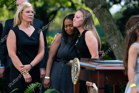 """Stock Image of Shannon Terranova, right, ex-wife of USCP Officer William """"Billy"""" Evans hugs Anne Winters, sister of USCP Officer Howard Liebengood after President Joe Biden signed a bill that awards Congressional gold medals to law enforcement officers that protected members on Congress at the Capitol during the Jan. 6 riots, in the Rose Garden of the White House, in Washington"""